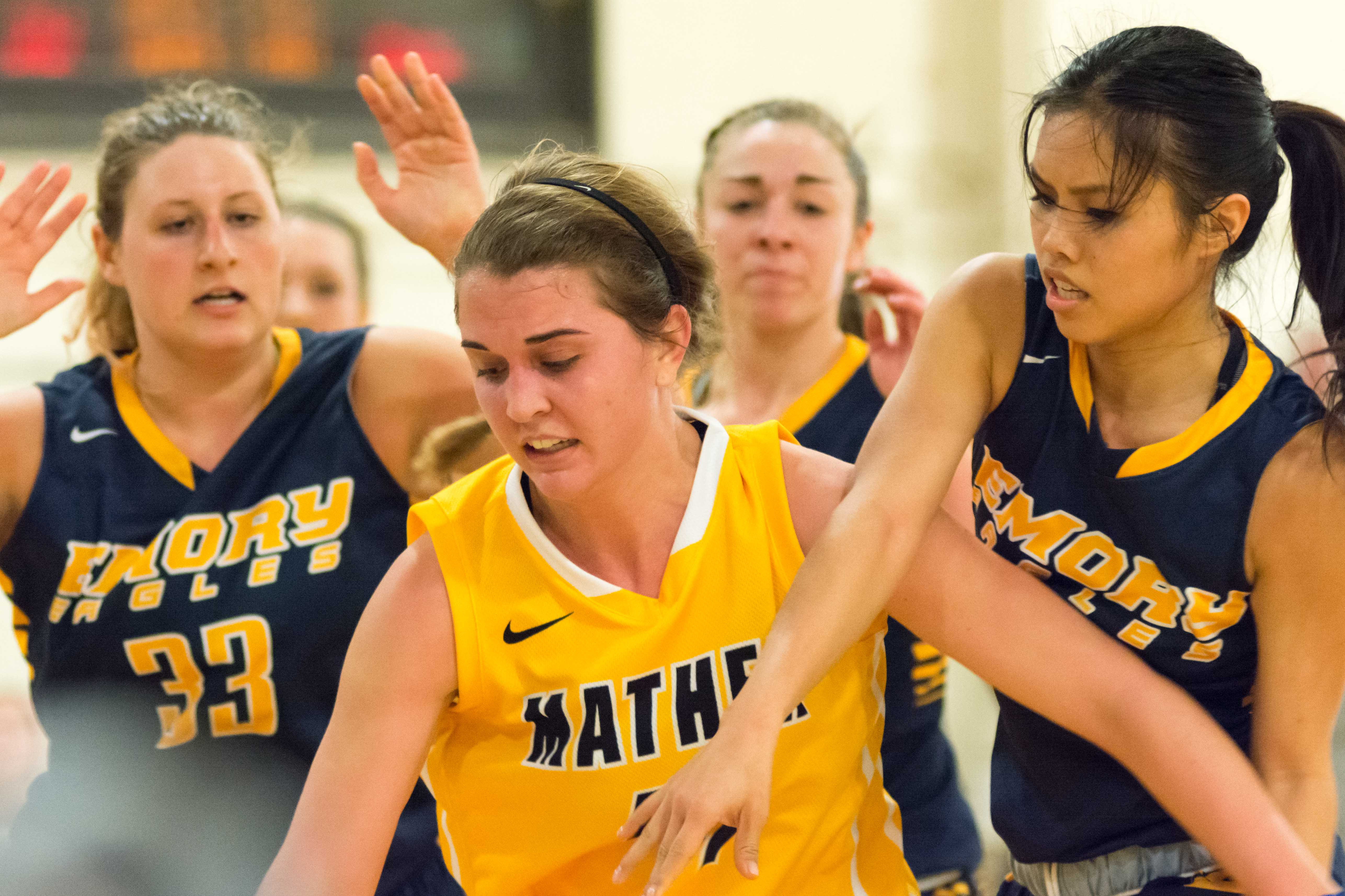 Brooke Orcutt is swarmed by Emory defenders in the opening game of Throwback weekend. Orcutt and the Spartans wore Mather College uniforms for the weekend.