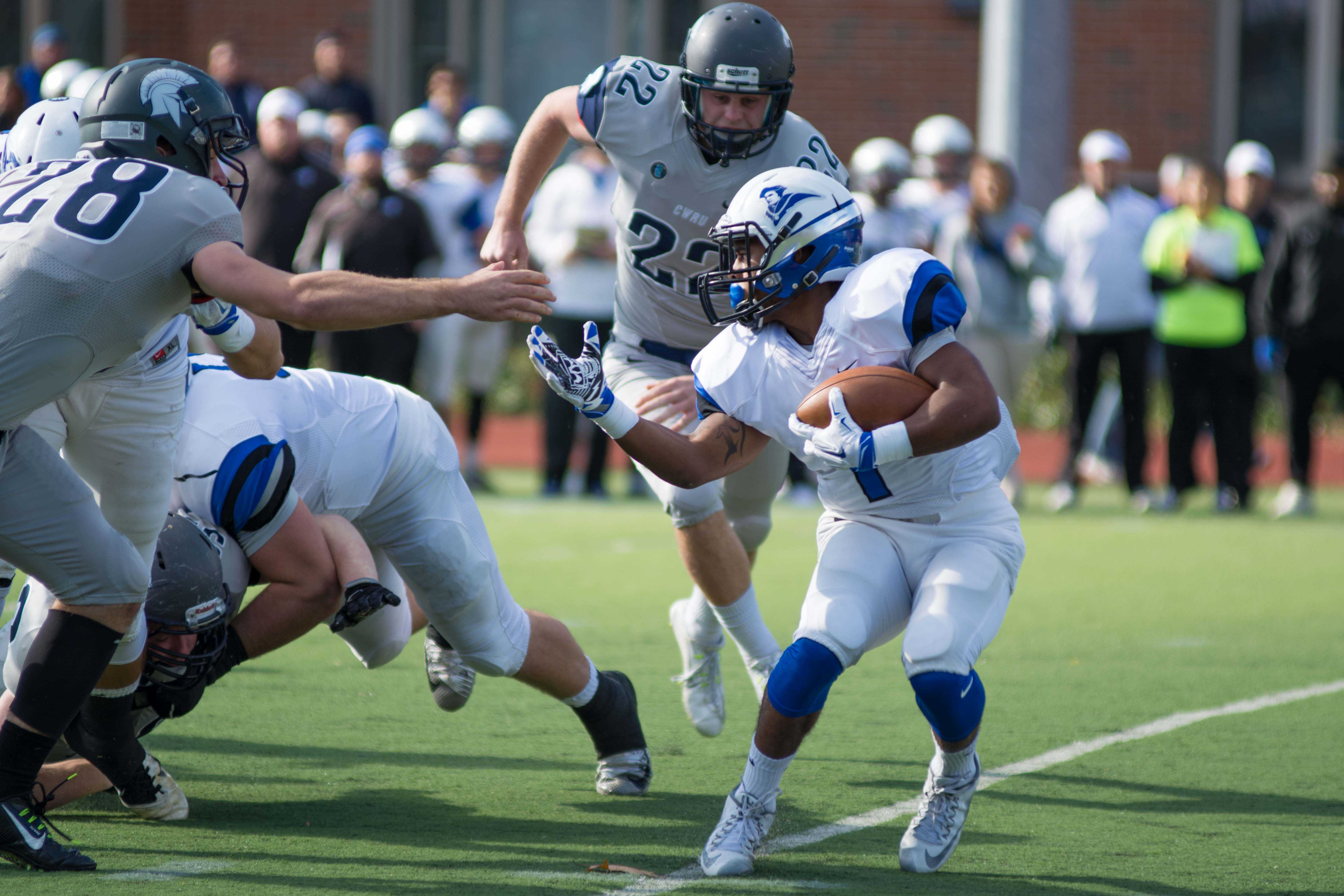 Spartan defender attempts to stop the Thomas More ball carrier.