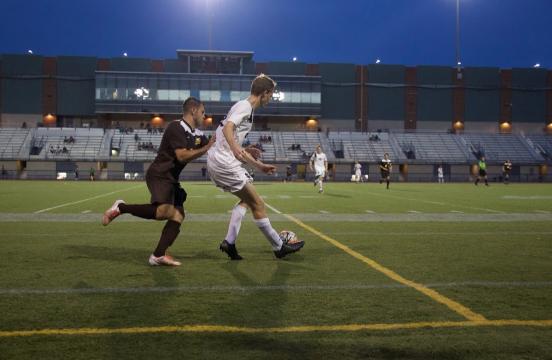 Second-year defender Christian Lytle tries to clear the ball as an opponent attacks him from behind.