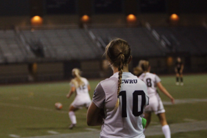 Fourth-year Anne Backlund looks on as teammates battle for possession. The women's soccer team wrapped up their season on Nov. 5 with a 2-0 loss.