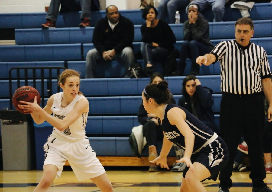 First-year+guard+Marissa+Muth+searches+for+a+teammate+past+a+Brandeis+defender.