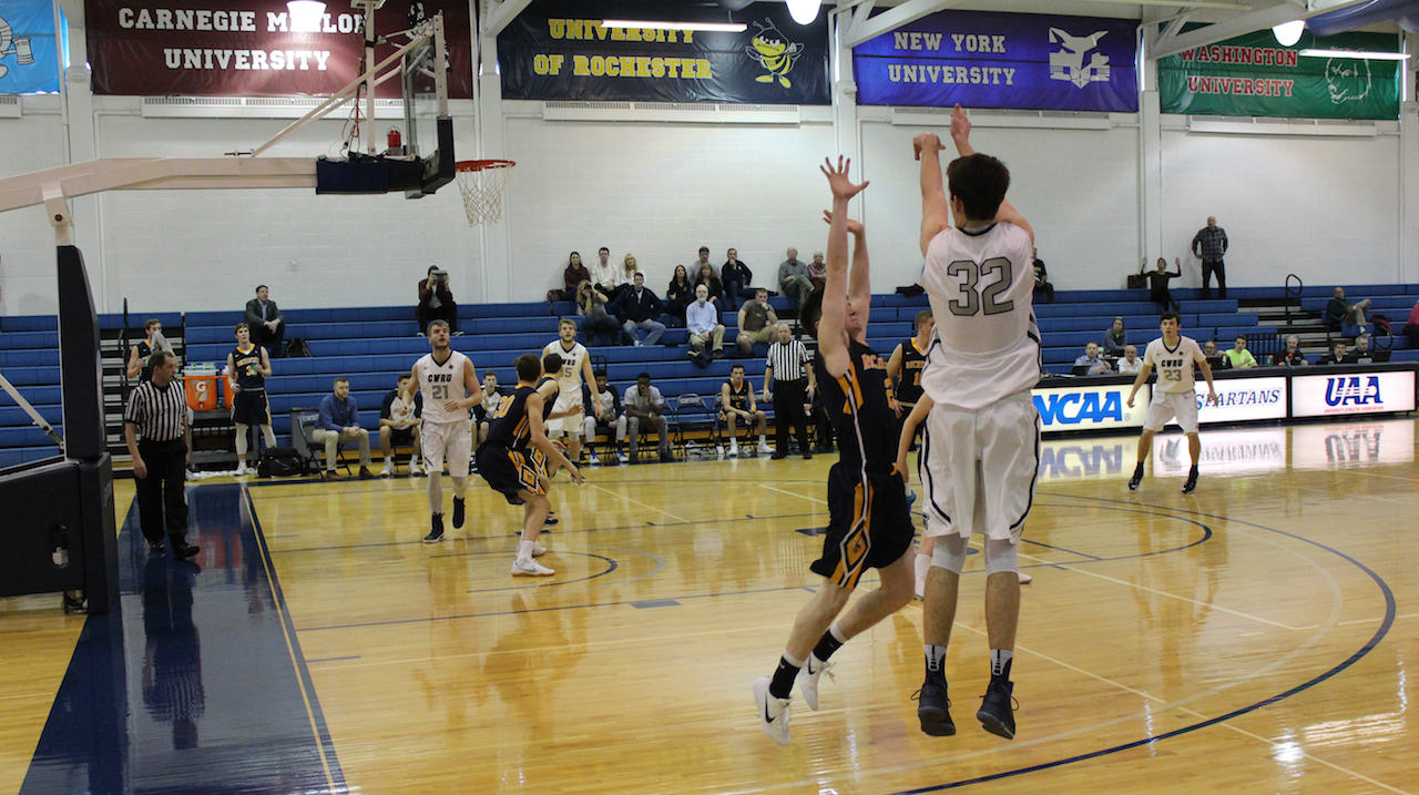 Connor Nally shoots a three-pointer with a hand in his face.