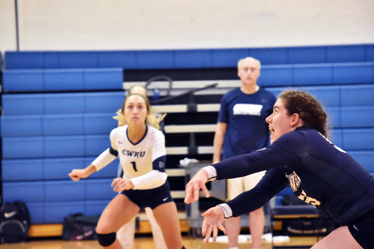 Noel Jeansonne frantically dives for the ball during the team's match against Baldwin Wallace; Haley Sims looks across the court after going up for a kill.