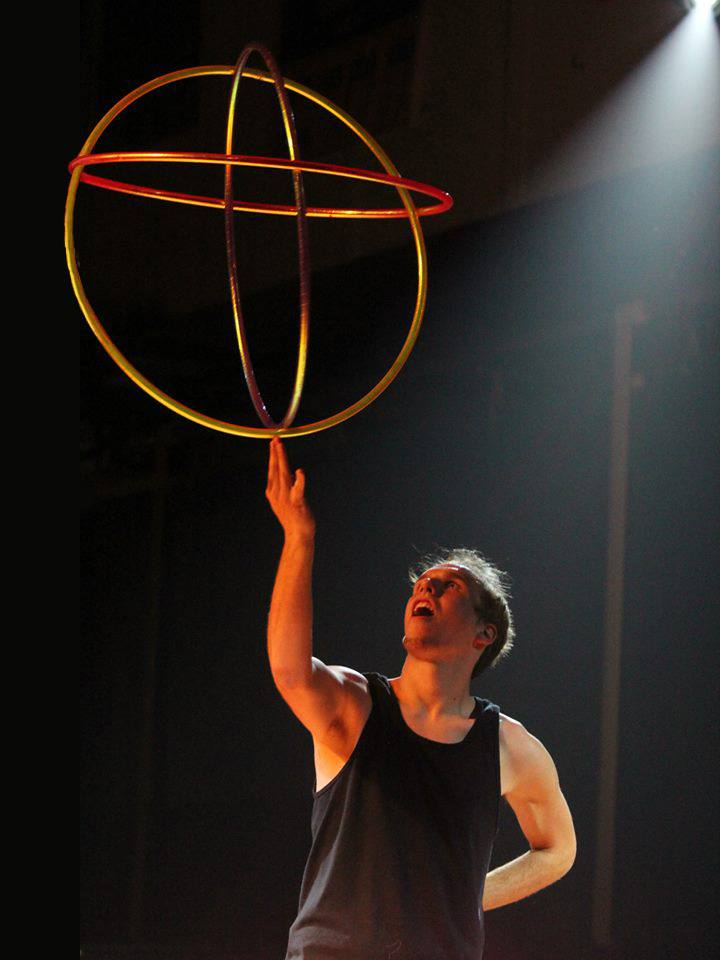 Benjamin Berry, hoop dancer and feature performer, claims the title of ringmaster as he skillfully balances a set of hoops on the tips of his fingers all the while staring in awe at his own feat.