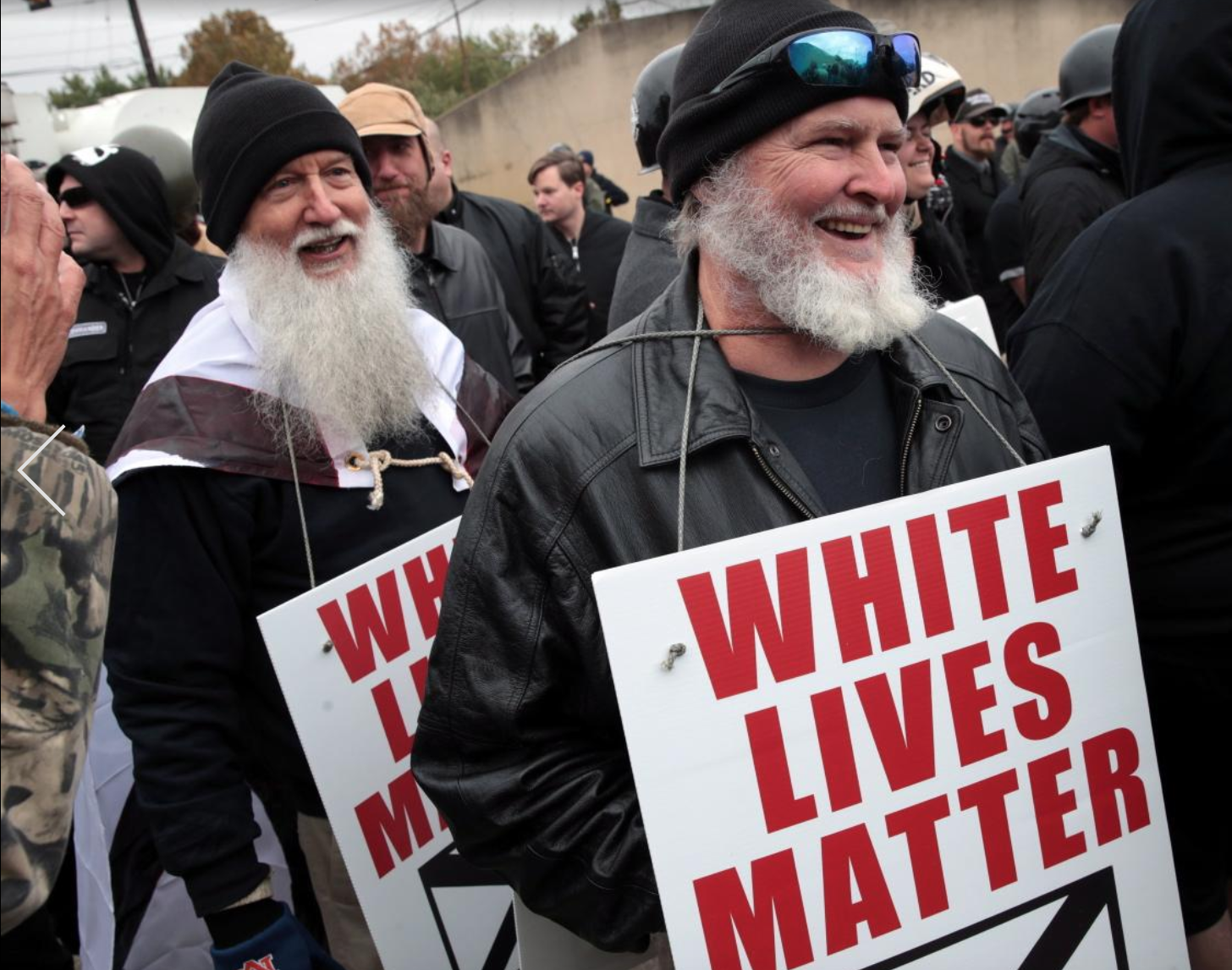 Protesters hold up signs displaying the White Lives Matter slogan.