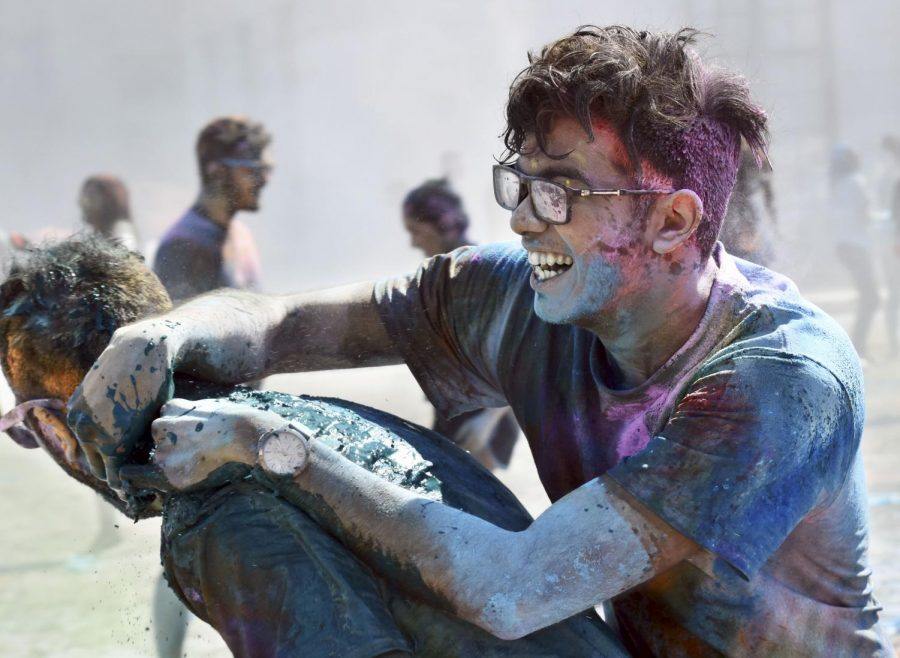 Two+participants+of+Holi+enjoy+the+warm+day+while+covered+in+pigments+of+color.