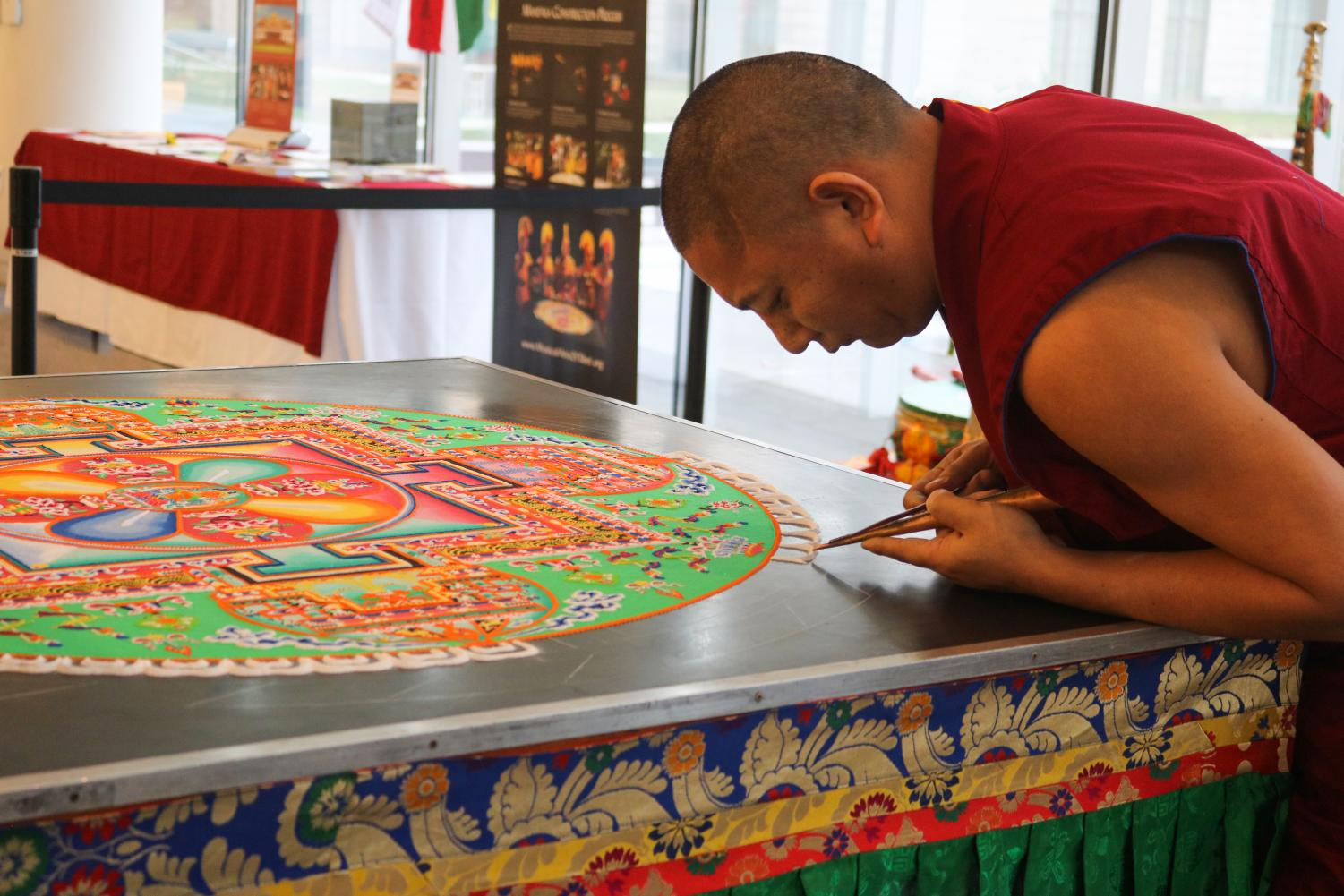 A monk uses a chak-pur, a traditional metal funnel, to pour grains of sand needed to construct the mandala.
