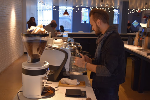 A barista behind the counter of Blue Sky Brews, which opened its doors on Feb. 7.