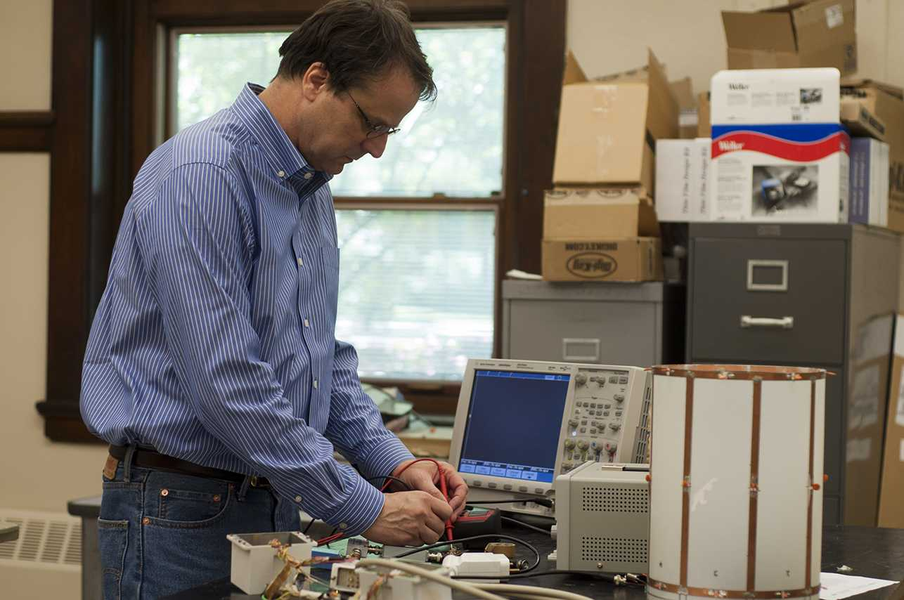 Associate Professor of Physics Michael Martens works in his medical imaging physics lab. He is looking to develop cheaper MRI technology, primarily by designing a scanner that uses less liquid hydrogen, a costly substance) as a coolant.