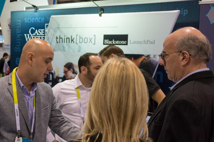 The SpiroSano team shows their platform to two visitors to the CWRU booth area