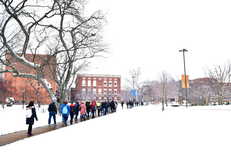 On the main quad, students are walking to classes in snow.