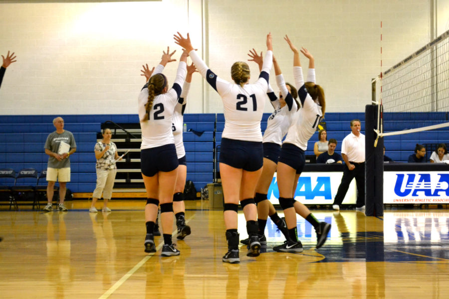 Members of the the volleyball team raise their hands to celebrate an ace last season.
