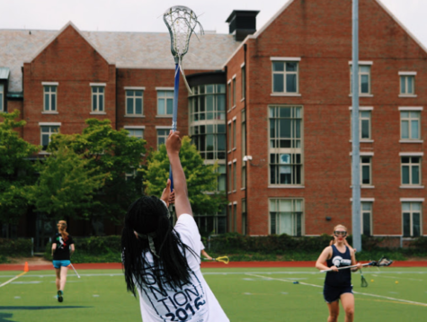A participant of the lacrosse clinic stretches to catch a pass during offensive drills.