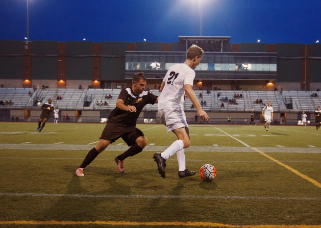 Trying to keep the ball away from a close defender, midfielder Christian Lytle passes the ball to a teammate.
