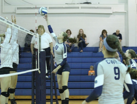 Attempting to clear two defenders, first-year Haley Sims tips the ball over the net.