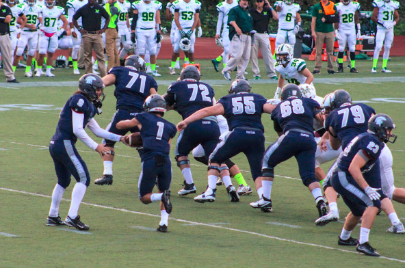 Third-year quarterback Rob Cuda hands off to second-year wide receiver Justin Phan early in the game against St. Vincent. The Spartans successful running attack was key to their victory.