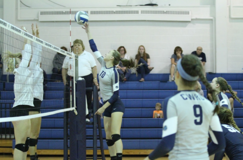 Karley King looks on as Haley Sims reaches for the ball, trying to bury a kill past two defenders.