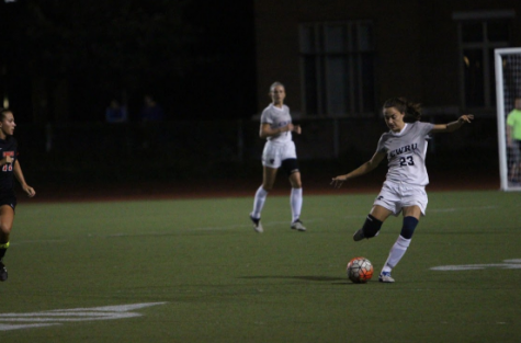 Looking to move the ball down the field, fourth-year defender Madeline Pollifrone rears back to strike the ball during a home match earlier this season.