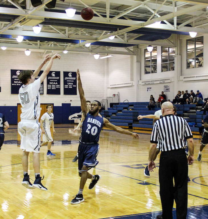 First-year forward Michael Hollis shoots over a Brandeis defender earlier this season.
