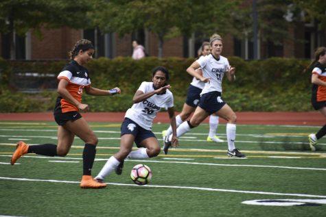 Defensman Melanie Cruicitt battles an opponent; following an attacker, defenseman Neha Cheemalavagu pursues the ball in order to stop a goal.