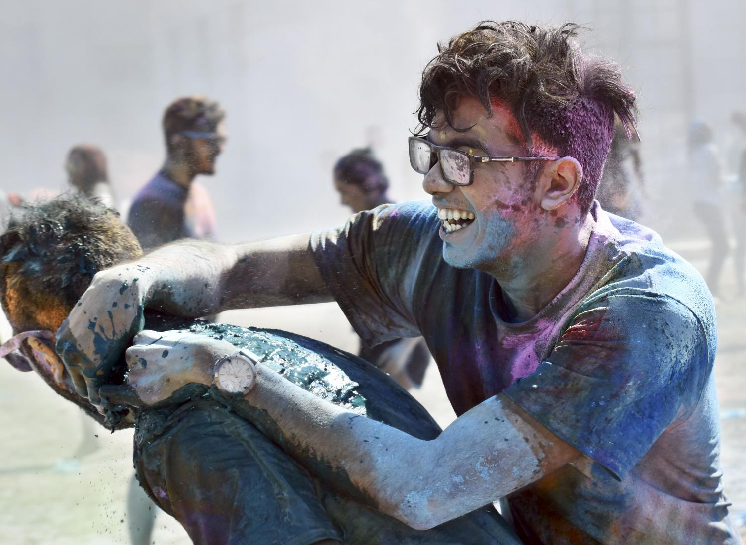 Two participants of Holi enjoy the warm day while covered in pigments of color.